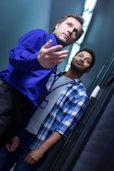 Симпатичные красивые коллеги-мужчины стоят вместе и с нетерпением ждут, пока находятся в серверной