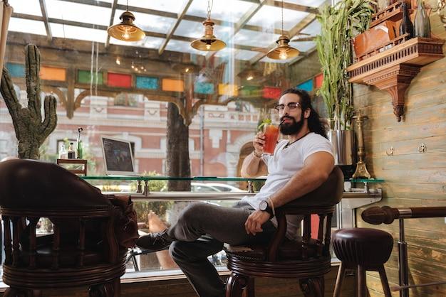 Красивый красивый мужчина пьет кофе во время отдыха в кафе