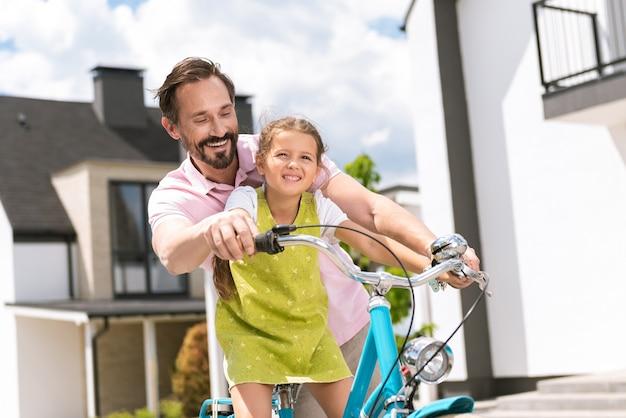 자전거를 타고 그녀를 가르치는 동안 그의 딸 뒤에 서있는 좋은 잘 생긴 남자