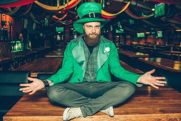 聖パトリックのスーツを着た素敵なハンサムな若いひげを生やした男は、パブのテーブルで足を組んで座っています。彼のコスチュームは緑。男のポーズ。