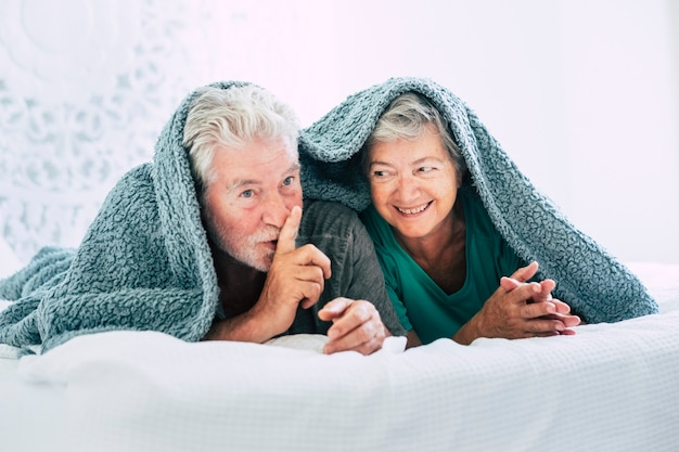 Nice happy beautiful mature couple in the bedroom lay down in the bed stay under the cover and say silence to the camera
