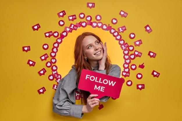 赤い髪の素敵な幸せなヨーロッパの女性はインターネットでブログをフォローするように頼む
