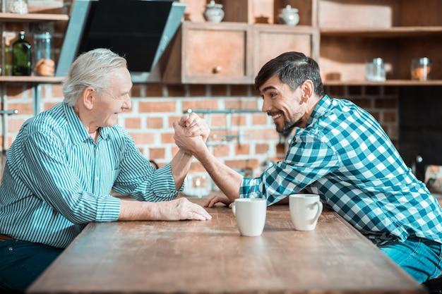 좋은 행복한 긍정적 인 아버지와 아들이 서로 마주 앉아 팔씨름을하면서 누가 더 강한 지 결정합니다.