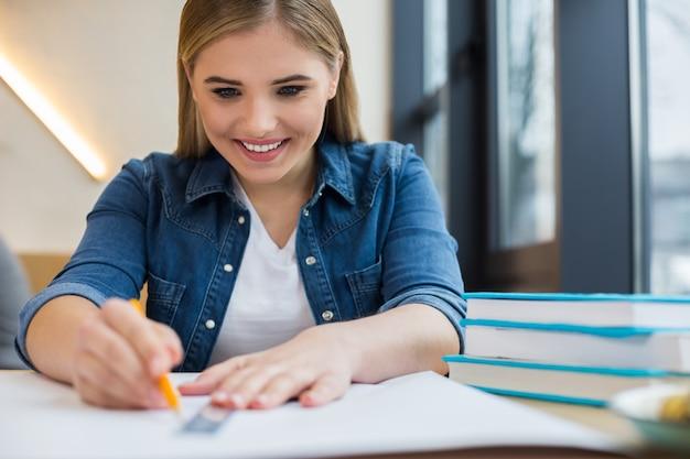 테이블에 앉아 그녀의 프로젝트에서 작업하는 동안 그림을하고 좋은 행복 긍정적 인 여자