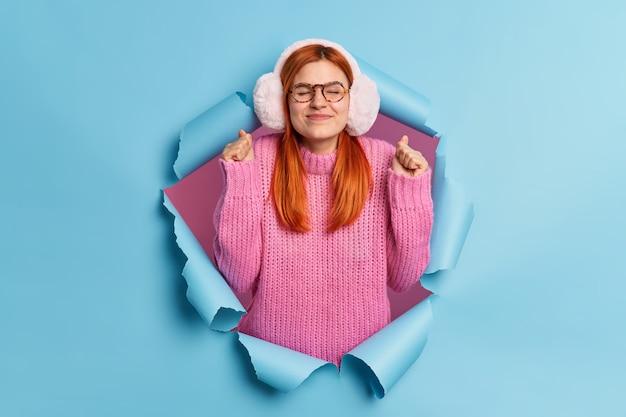 좋은 희망을 가진 빨간 머리 여자는 주먹을 쥐고 아주 좋은 일이 일어날 것으로 예상하고 겨울 귀마개를 착용하고 니트 점퍼가 찢어진 종이를 뚫습니다.