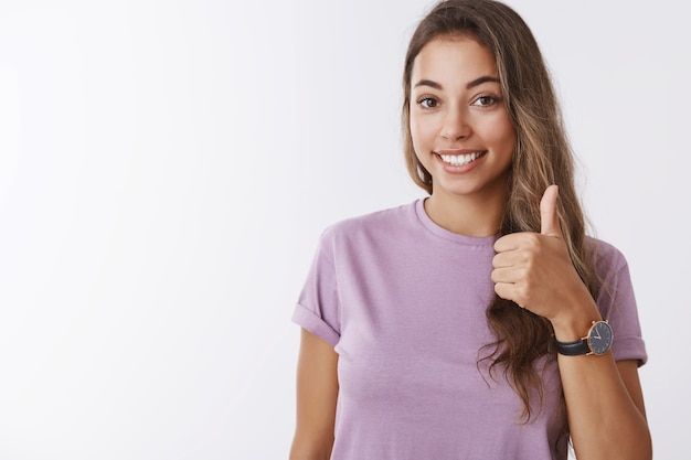 Nice i in. friendly outgoing gorgeous young smiling girl showing thumb up saying yes, approving liking awesome interesting plan, grinning accepting terms, no problems, standing white wall