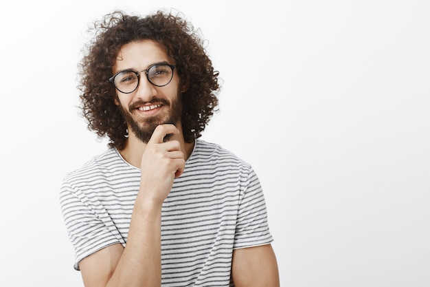 Nice idea, you intrigued me. portrait of interested smart handsome adult man with beard and curly hair in trendy glasses