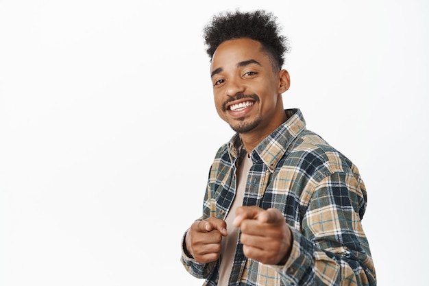 Nice job, congrats. smiling handsome african american boy, guy pointing fingers with satisfied cheerful face, congratulating you, praise nice work on white.