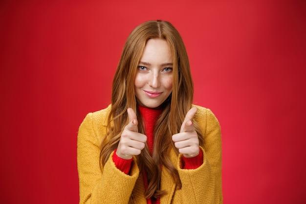 Bel lavoro è stato fantastico. ritratto di donna rossa sfacciata e sfacciata di bell'aspetto con lentiggini e occhi azzurri che sorridono sensualmente con un sorriso soddisfatto che mostra i pollici in su in segno di approvazione e come gesto.