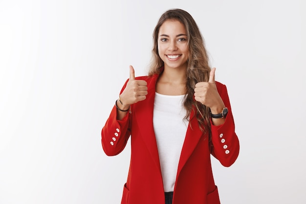 Nice job, well done, great. proud good-looking satisfied female entrepreneur showing thumbs up smiling delighted pleased seeing good result, encouraging assitant keep up, liking plan, approving