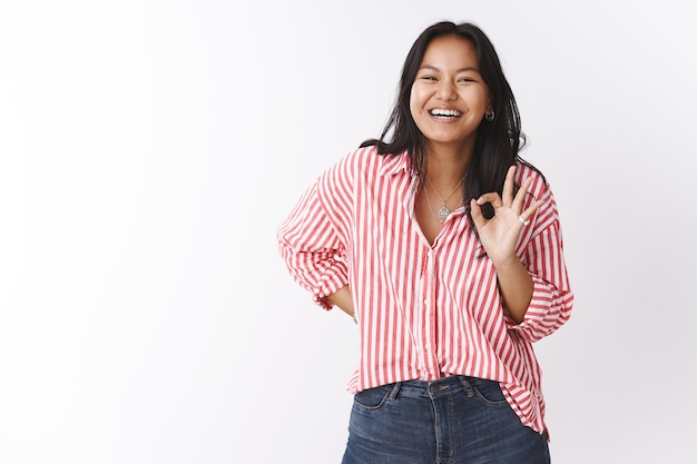 Nice joke. portrait of amused gorgeous malasian female in striped blouse having fun laughing out loud from joy hearing funny joke showing okay sign as checking out cool prank over white wall