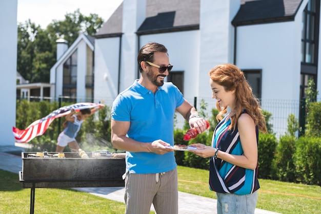 Хороший радостный мужчина улыбается своей жене, кладя кетчуп на ее тарелку