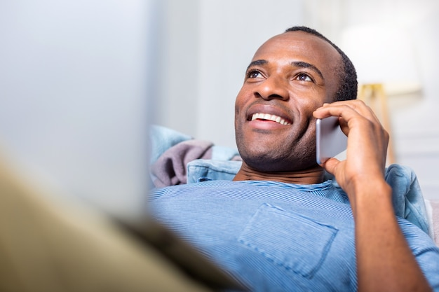 Приятный радостный позитивный мужчина улыбается и держит свой смартфон во время телефонного разговора