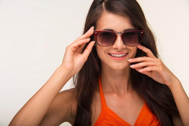 Милая дама в оранжевой рубашке улыбается.
