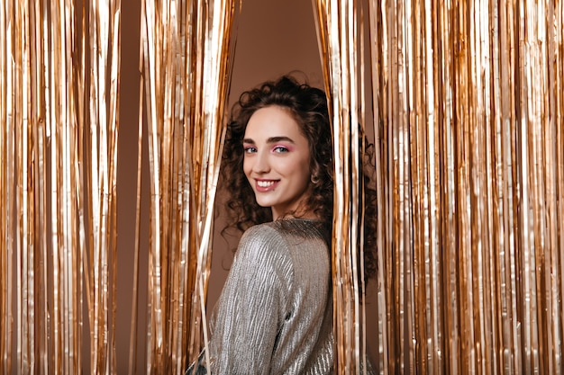 Bella signora in abito d'argento sorridente su sfondo oro