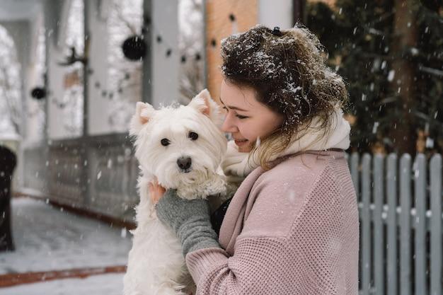 面白いかわいい感情で愛らしい白い犬を抱き締める素敵な笑いの女の子。ウエストハイランドホワイトテリア。採用コンセプト。