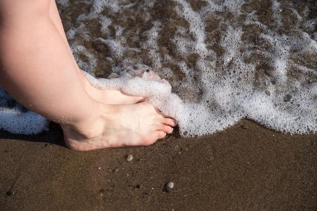 水の中を歩いているかわいい女の子の素敵な足。