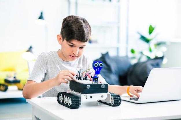 Симпатичный маленький мальчик использует свой ноутбук, экспериментируя с роботизированными технологиями