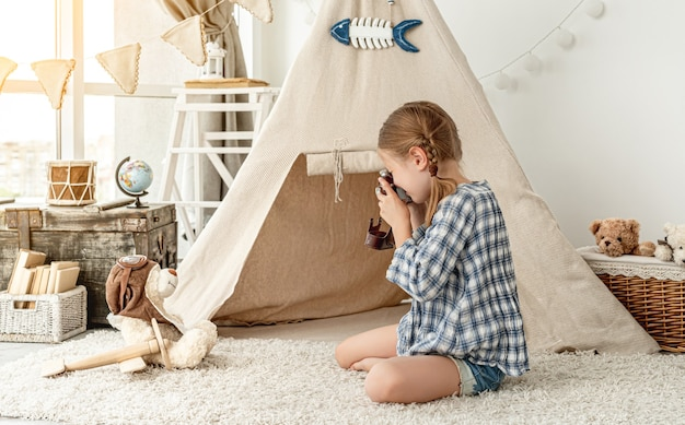 Nice little girl photographing plush teddy on wigwam installed in playroom surface
