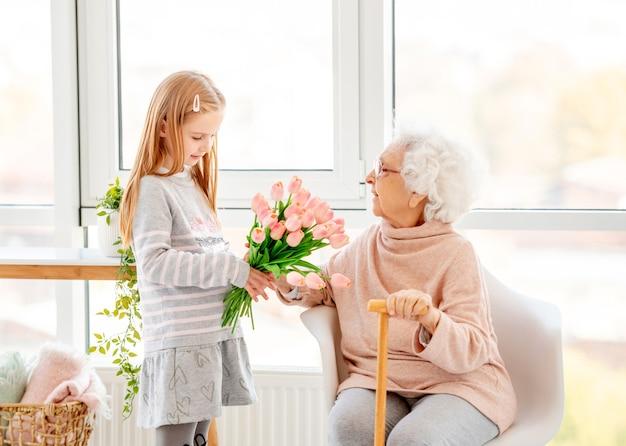 明るい部屋で彼女の祖母に花束を提示する素敵な女の子