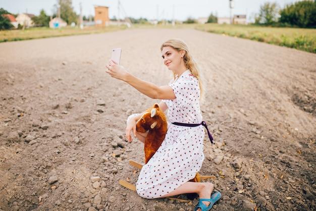 フィールドのおもちゃの馬に座っている間スマートフォンでselfie写真を作る素敵な美しいブロンドの女の子。