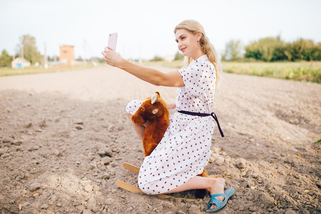 Nice looking beautiful blonde girl making selfie photo on phone. young happy pretty female in stylish retro dress riding toy horse outdoor.