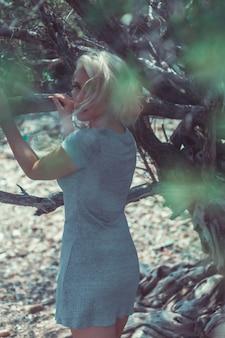 ラーン島のタイ湾の海岸のツリーでポーズをとって灰色のドレスで素敵な金髪観光女の子。
