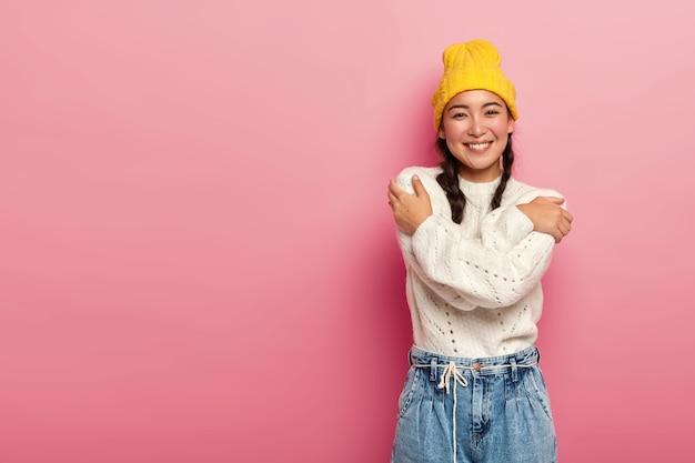 멋진 찾고 사랑스러운 여자가 자신을 포옹하고, 이빨 미소를 짓고, 가슴 위에 손을 교차하고, 분홍색에 고립 된 노란 모자를 쓰고 있습니다.