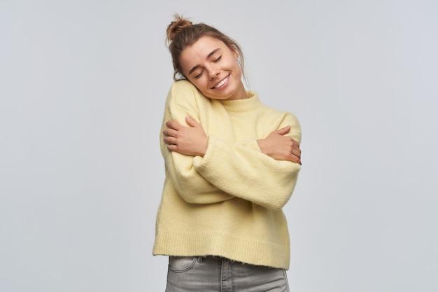 Bella donna, bella ragazza con i capelli biondi raccolti in una crocchia. indossare un maglione giallo. abbraccia se stessa, si sente calda e a suo agio. mantiene gli occhi chiusi. stand isolato su un muro bianco