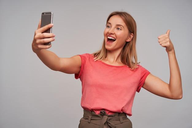 좋은 찾고 여자, 금발 머리를 가진 아름다운 소녀. 분홍색 티셔츠와 갈색 치마를 입고. 셀카 만들기, 넓게 미소 짓고 회색 벽 위에 엄지 표시