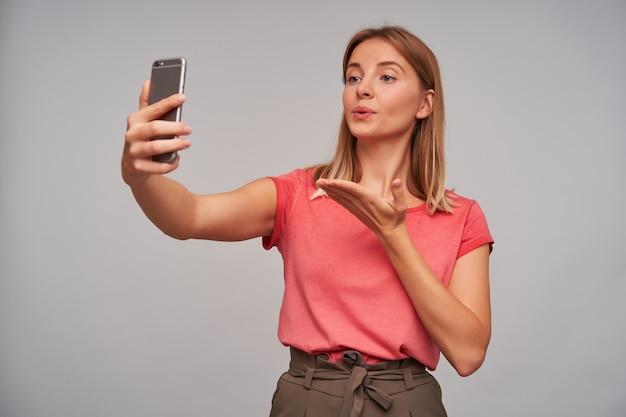 좋은 찾고 여자, 금발 머리를 가진 아름다운 소녀. 분홍색 티셔츠와 갈색 치마를 입고. 셀카 만들기, 친구와 채팅, 회색 벽에 공기 키스 보내기