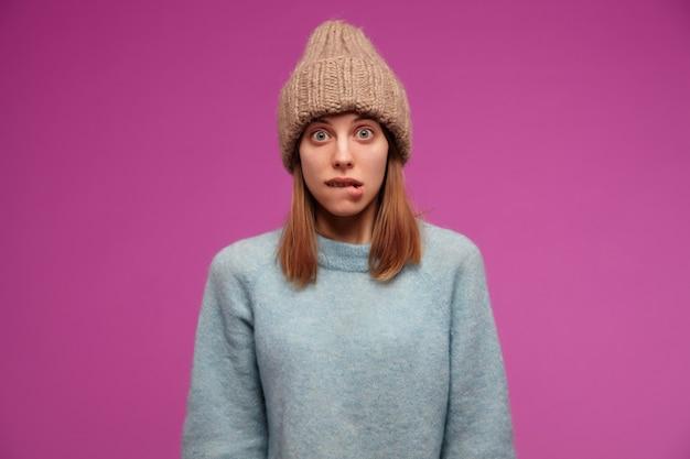 Bella donna, bella ragazza con i capelli castani. indossare maglione blu e cappello lavorato a maglia. flirty che si morde un labbro sul muro viola