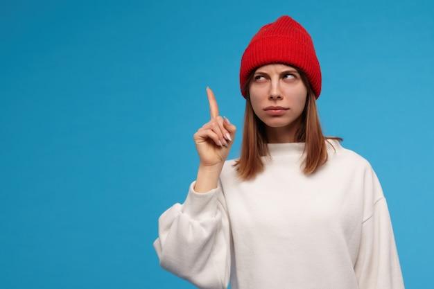 좋은 찾고 여자, 갈색 머리를 가진 아름다운 소녀. 흰색 스웨터와 빨간 모자를 쓰고. 손가락을 들고 아이디어를 얻었습니다. 복사 공간에서 왼쪽으로보고, 파란색 벽 위에 절연