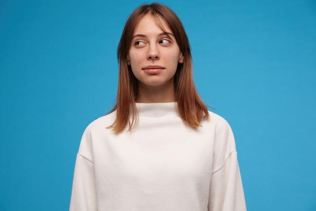 좋은 찾고 여자, 갈색 머리를 가진 아름다운 소녀. 흰색 스웨터를 입고. 사람들이 개념. 캐주얼 찾고. 파란색 벽 위에 고립 된 복사 공간에서 왼쪽을 의심스럽게보고