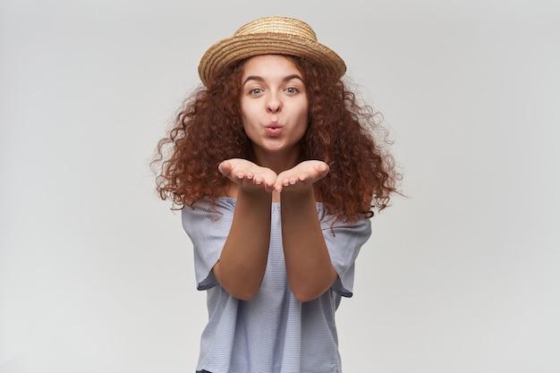 見栄えの良い女性、巻き毛の生姜髪の美しい少女。ストライプのオフショルダーブラウスと帽子を着用。あなたにエアキスを送る。白い壁に隔離