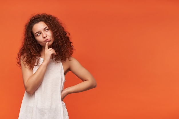 Nice looking woman, beautiful girl with curly ginger hair. wearing white off-shoulder blouse. touching her lip and thinking. watching to the right at copy space, isolated over orange wall