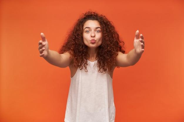 좋은 찾고 여자, 곱슬 생강 머리를 가진 아름다운 소녀. 흰색 오프 숄더 블라우스를 입고 있습니다. 당신을 포옹하고 키스하려고합니다. 사랑을 퍼 뜨리다. 오렌지 벽 위에 절연