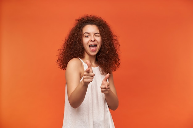 見栄えの良い女性、巻き毛の生姜髪の美しい少女。白いオフショルダーのブラウスを着ています。オレンジ色の壁に隔離されたあなたにウィンク