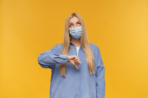 Nice looking woman, beautiful girl with long blond hair shows thumbs down sign. wearing blue shirt and medical face mask. watching up at copy space, isolated over orange background