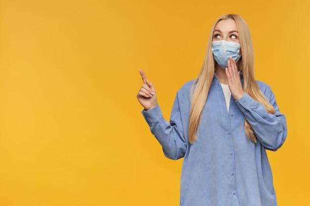 좋은 찾고 여자, 긴 금발 머리를 가진 아름다운 소녀. 파란색 셔츠와 의료용 얼굴 마스크를 착용. 카메라를보고 오렌지 배경 위에 고립 된 복사 공간에서 왼쪽을 가리키는