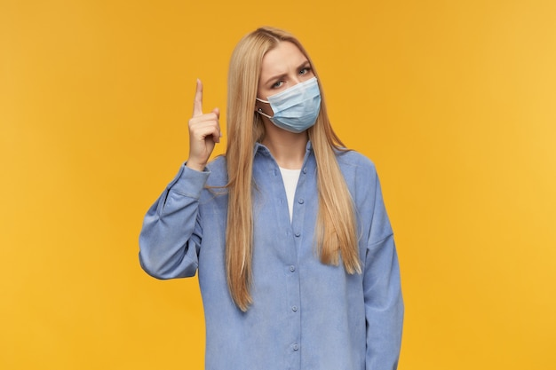 Nice looking woman, beautiful girl with long blond hair. wearing blue shirt and medical face mask. people and emotion concept. pointing with finger upwards isolated over orange background