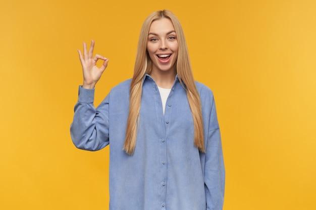 Симпатичная женщина, красивая девушка с длинными светлыми волосами. в синей рубашке. концепция людей и эмоций. показываю, что все в порядке, хороший знак. смотрю в камеру, изолированные на оранжевом фоне