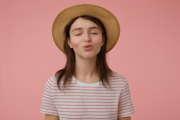 Bella donna dall'aspetto, bella ragazza con lunghi capelli castani. indossare t-shirt con strisce rosse e cappello. baciarti ad occhi chiusi. concetto emotivo. stai isolato su un muro rosa pastello