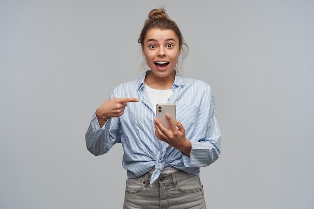 Bella donna, ragazza eccitata con i capelli biondi raccolti in una crocchia. indossa maglietta annodata a righe e tiene in mano uno smartphone indicando il suo telefono. guardando la telecamera, isolata sul muro grigio