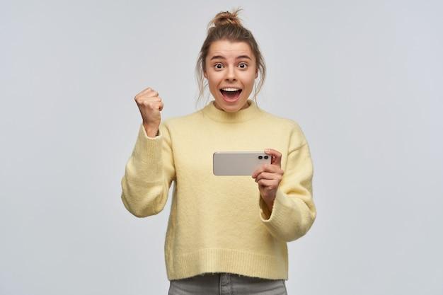 좋은 찾고 여자, 금발 머리를 가진 흥분된 여자가 롤빵에 모였다. 노란색 스웨터를 입고 스마트 폰을 들고. 그녀의 주먹을 들어 축하해. 흰 벽에 고립 된 카메라를 보면