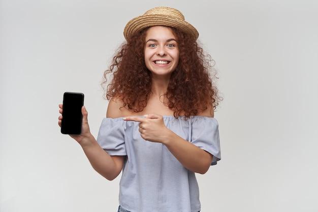 Bella donna, ragazza con i capelli ricci di zenzero. indossare camicetta e cappello a righe con spalle scoperte. tenendo e indicando lo smartphone, copia dello spazio. isolato su muro bianco