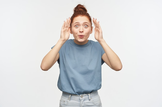 Nice looking woman, playful girl with ginger hair gathered in a bun. wearing blue t-shirt and jeans. playing hide and seek, uncover her face.  isolated over white wall