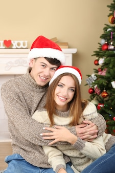 クリスマスツリーの近くの素敵な愛のカップル。クリスマスを祝う女性と男性