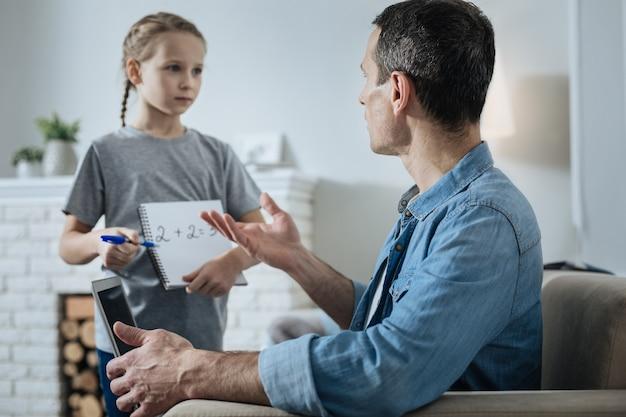 노트북을 들고 그녀의 아빠 근처에 서서 그가 일하는 동안 수학에 대한 도움을 요청하는 멋진 사랑스러운 fair-haired 어린 소녀