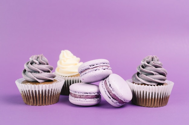 Nice macaroons near cupcakes